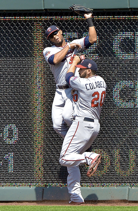 Minnesota Twins center fielder Aaron Hicks catches a fly ball for an out as he collides with teammate Chris Colabello