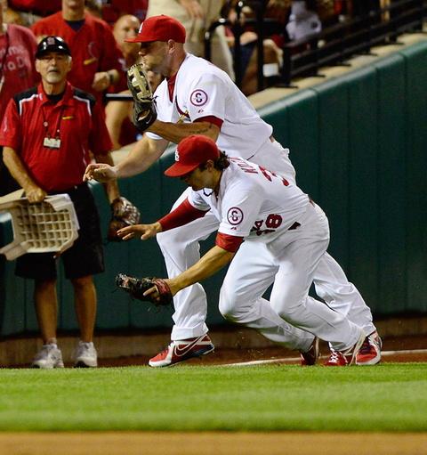 Matt Holliday of the St. Louis Cardinals catches a fly ball then collides with Pete Kozma
