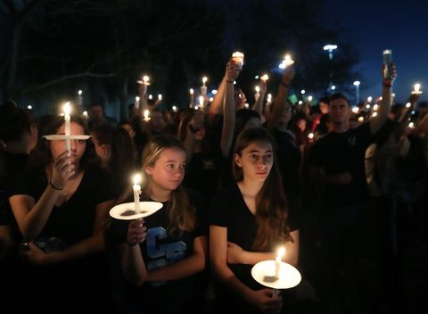 Students and family members hold candles during a vigil for victims of the mass shooting at Marjory Stoneman Douglas High School, at Pine Trail Park, in Parkland, Florida.